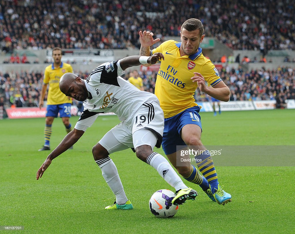 <a gi-track='captionPersonalityLinkClicked' href=/galleries/search?phrase=Jack+Wilshere&family=editorial&specificpeople=5446655 ng-click='$event.stopPropagation()'>Jack Wilshere</a> of Arsenal closes down Dwight Tiendalli of Swansea during the Barclays Premier League match between Swansea and Arsenal at Liberty Stadium on September 28, 2013 in Swansea, Wales.