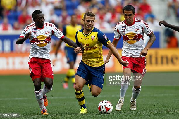 Jack Wilshere of Arsenal fights for the ball with Ambroise Oyongo and Tim Cahill of New York Red Bulls during their friendly match at Red Bull Arena...