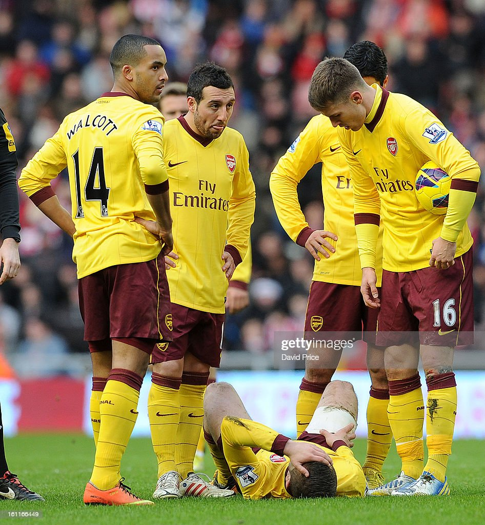 Jack Wilshere of Arsenal hold his head in his hands after getting an injury as Theo Walcott, Santi Cazorla and Aaron Ramsey of Arsenal suround him during the Barclays Premier League match between Sunderland and Arsenal at Stadium of Light on February 09, 2013 in Sunderland, England.