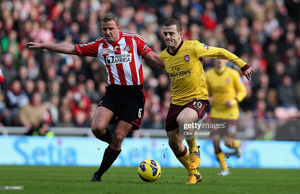 Jack Wilshere of Arsenal holds off a challenge from Lee Cattermole of Sunderland during the Barclays Premier League match between Sunderland and Arsenal at the Stadium of Light on February 9, 2013 in Sunderland, England.