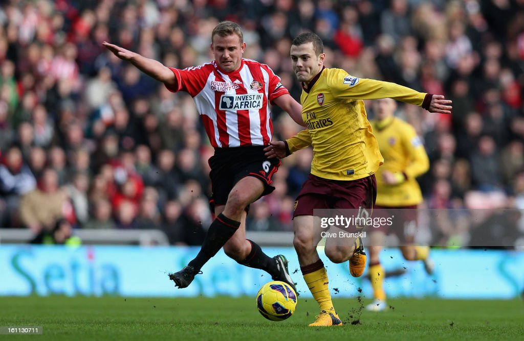 <a gi-track='captionPersonalityLinkClicked' href=/galleries/search?phrase=Jack+Wilshere&family=editorial&specificpeople=5446655 ng-click='$event.stopPropagation()'>Jack Wilshere</a> of Arsenal holds off a challenge from <a gi-track='captionPersonalityLinkClicked' href=/galleries/search?phrase=Lee+Cattermole&family=editorial&specificpeople=646988 ng-click='$event.stopPropagation()'>Lee Cattermole</a> of Sunderland during the Barclays Premier League match between Sunderland and Arsenal at the Stadium of Light on February 9, 2013 in Sunderland, England.