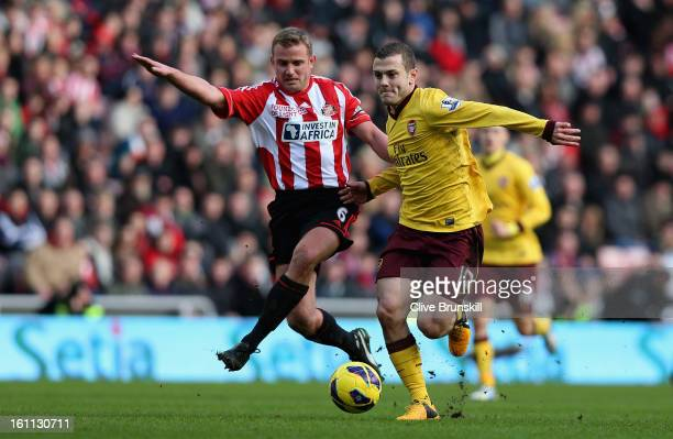 Jack Wilshere of Arsenal holds off a challenge from Lee Cattermole of Sunderland during the Barclays Premier League match between Sunderland and...