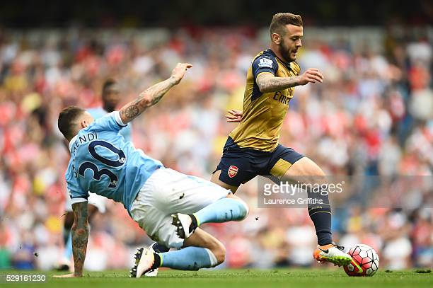 Jack Wilshere of Arsenal holds off Nicolas Otamendi of Manchester City during the Barclays Premier League match between Manchester City and Arsenal...