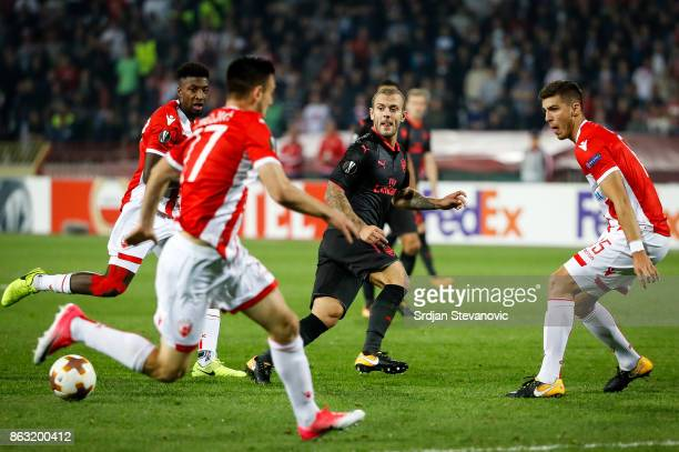 Jack Wilshere of Arsenal in action against Srdjan Babic and Mitchell Donald of Crvena Zvezda during the UEFA Europa League group H match between...