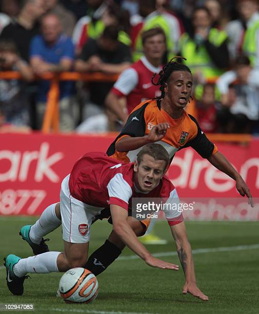 Jack Wilshere of Arsenal ingets tackled by Sam Cox of Barnet during the preseason friendly match between Barnet and Arsenal at Underhill on July 17...