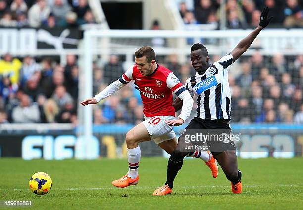 Jack Wilshere of Arsenal is challenged by Cheick Tiote of Newcastle United during the Barclays Premier League match between Newcastle United and...