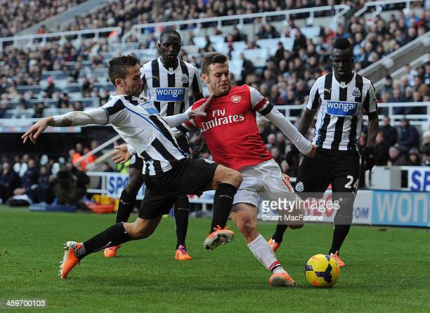 Jack Wilshere of Arsenal is challenged by Yohan Cabaye Moussa Sissoko and Cheick Tiote of Newcastle during the Barclays Premier League match between...