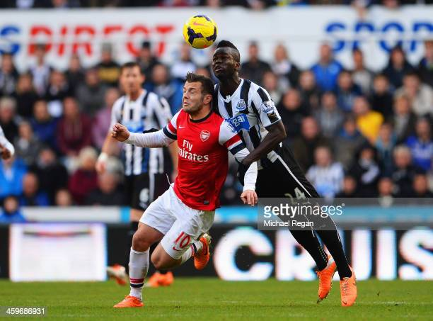 Jack Wilshere of Arsenal is challenged for a header by Cheick Tiote of Newcastle United during the Barclays Premier League match between Newcastle...