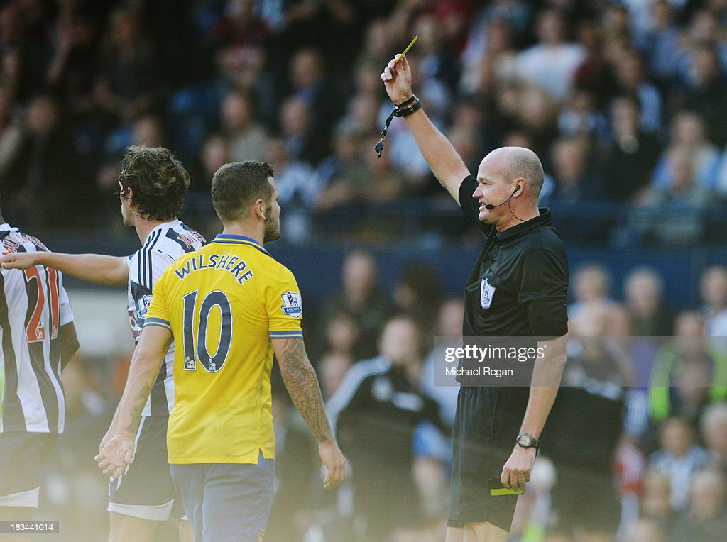 Jack Wilshere of Arsenal is shown a yellow card by referee Lee Mason and is booked during the Barclays Premier League match between West Bromwich Albion and Arsenal at The Hawthorns on October 6, 2013 in West Bromwich, England.