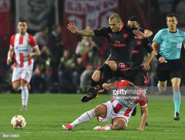 Jack Wilshere of Arsenal jumps over Red Star's Filip Stojkovic during the UEFA Europa League group H match between Crvena Zvezda and Arsenal FC at...