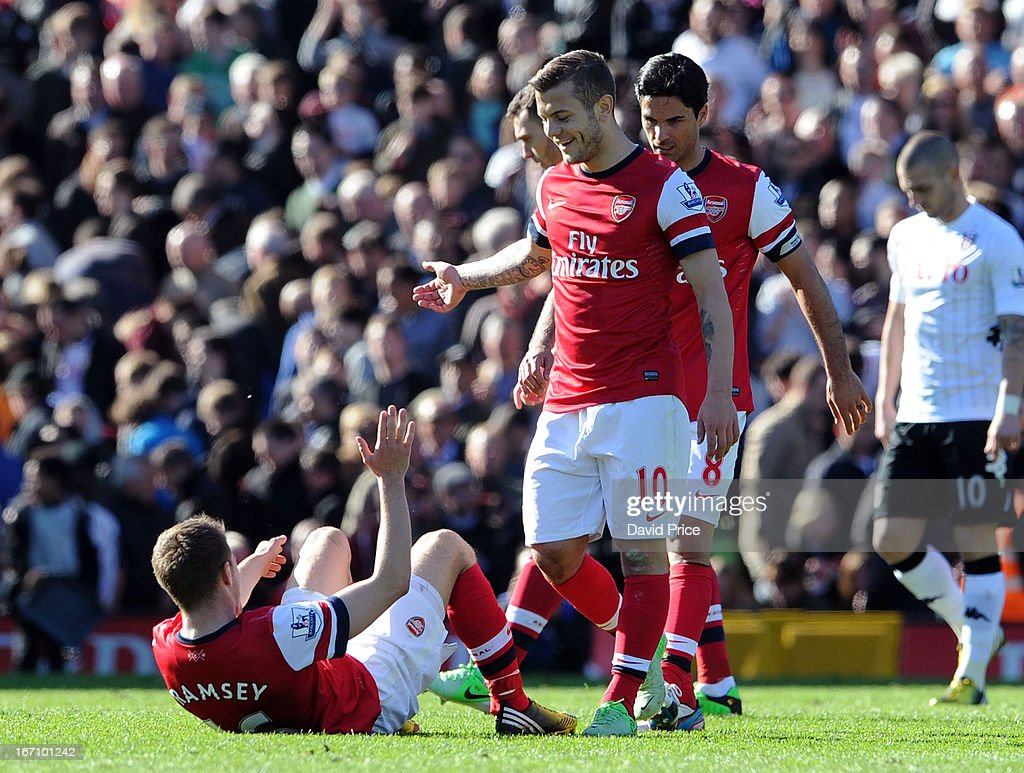 Jack Wilshere of Arsenal picks Aaron Ramsey up at the end of the Barclays Premier League match between Fulham and Arsenal at Craven Cottage on April 20, 2013 in London, England.