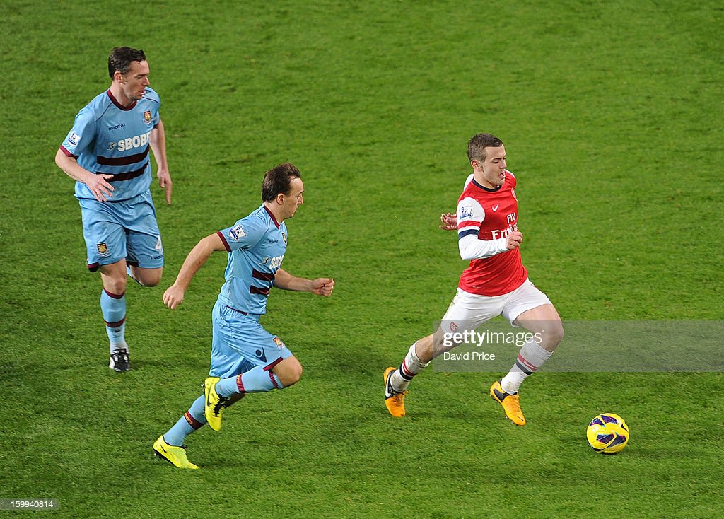 <a gi-track='captionPersonalityLinkClicked' href=/galleries/search?phrase=Jack+Wilshere&family=editorial&specificpeople=5446655 ng-click='$event.stopPropagation()'>Jack Wilshere</a> of Arsenal races away from <a gi-track='captionPersonalityLinkClicked' href=/galleries/search?phrase=Kevin+Nolan&family=editorial&specificpeople=206775 ng-click='$event.stopPropagation()'>Kevin Nolan</a> and <a gi-track='captionPersonalityLinkClicked' href=/galleries/search?phrase=Mark+Noble&family=editorial&specificpeople=844055 ng-click='$event.stopPropagation()'>Mark Noble</a> of West Ham during the Barclays Premier League match between Arsenal and West Ham United at Emirates Stadium on January 23, 2013 in London, England.