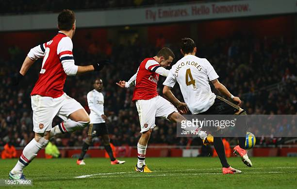 Jack Wilshere of Arsenal shoots past Chico Flores of Swansea City to score their first goal during the FA Cup with Budweiser Third Round Replay match...