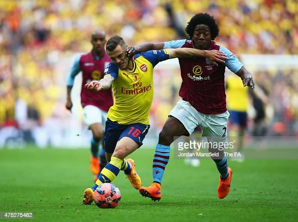 Jack Wilshere of Arsenal vies with Carlos Sanchez of Aston Villa during the FA Cup Final between Aston Villa and Arsenal at Wembley Stadium on May 30...