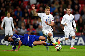 Jack Wilshere of England is tackled by Nicola Chiaruzzi of San Marino during the EURO 2016 Qualifier match between England and San Marino at Wembley...