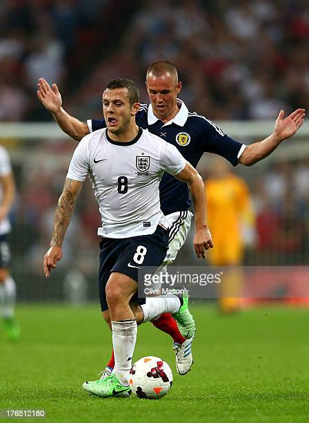Jack Wilshere of England resists a challenge from Kenny Miller of Scotland during the International Friendly match between England and Scotland at...