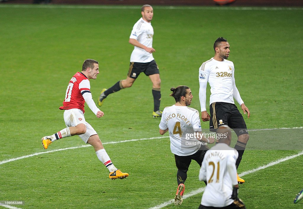 Jack Wilshere scores Arsenal's goal as Chico Flores and Kyle Bartley of Swansea look on during the FA Cup Third Round Replay match between Arsenal...