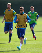 Jack Wilshere warms up during a Arsenal Training Session ahead of their Champions League fixture against Borussia Dortmund on September 15 2014 in St...