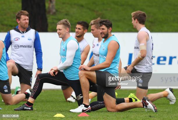 Jack Ziebell of the Kangaroos and Jarrad Waite of the Kangaroos stretch during a North Melbourne Kangaroos AFL training session at Arden Street...