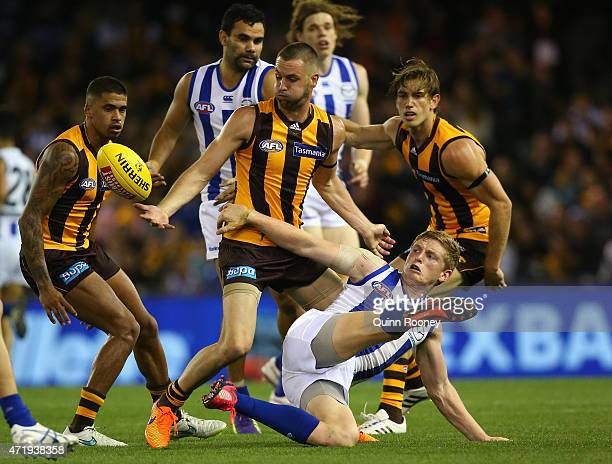 Jack Ziebell of the Kangaroos attempts to kick whilst being tackled by Matt Suckling of the Hawks during the round five AFL match between the North...