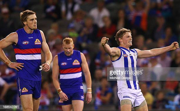 Jack Ziebell of the Kangaroos celebrates a goal next to Jordan Roughead and Adam Cooney of the Bulldogs during the round seven AFL match between the...