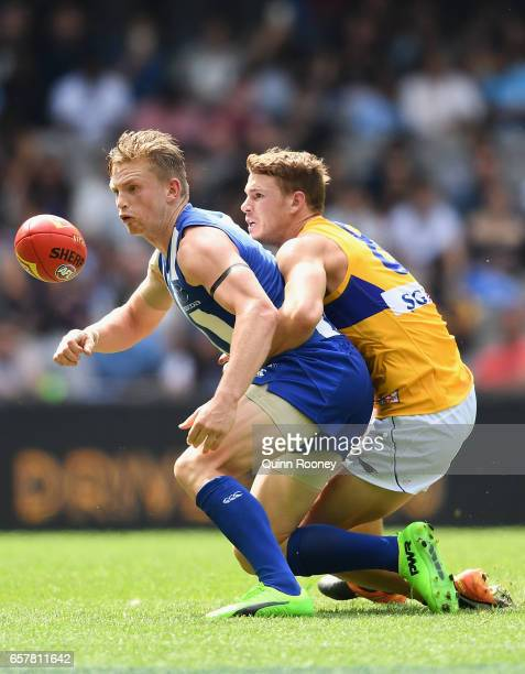 Jack Ziebell of the Kangaroos handballs whilst being tackled by Jack Redden of the Eagles during the round one AFL match between the North Melbourne...