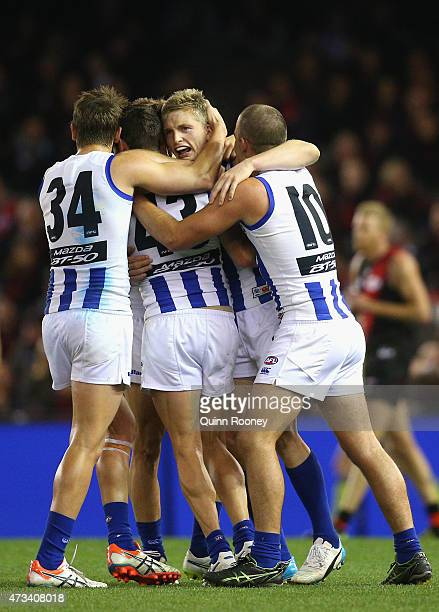 Jack Ziebell of the Kangaroos is congratulated by team mates after kicking a goal during the round seven AFL match between the Essendon Bombers and...