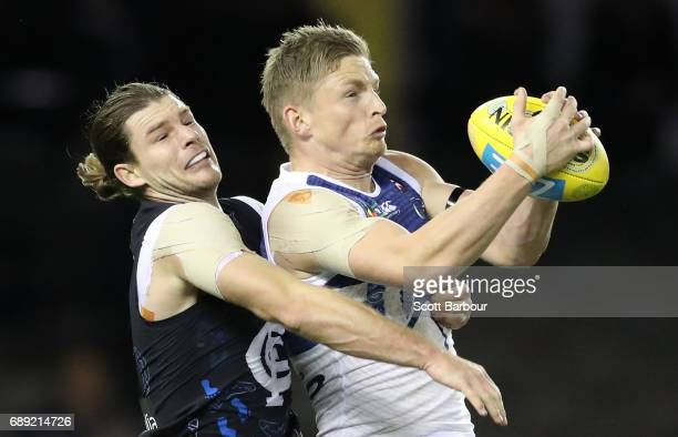 Jack Ziebell of the Kangaroos marks the ball in front of Bryce Gibbs of the Blues during the round 10 AFL match between the Carlton Blues and the...