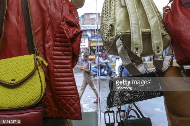 A jacket and bags are displayed in the window of a leather goods store in the Dharavi area of Mumbai India on Tuesday July 18 2017 India's new goods...