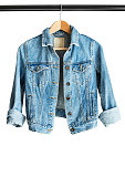 Blue denim jacket hanging on clothes rack isolated over white