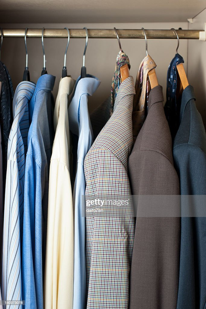 Jackets and shirts in closet : Stock Photo