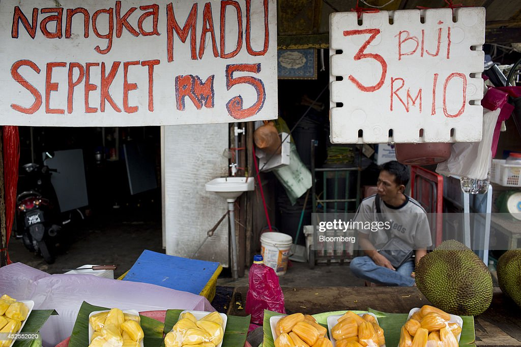 A jackfruit vendor sits at his stall at the Chow Kit wet market in Kuala Lumpur, Malaysia, on Tuesday, July 22, 2014. Malaysian Airline System Bhd. (MAS), reeling from its second disaster in four months, plans to present a revival plan to its state-run parent Khazanah Nasional Bhd. this week, people familiar with the matter said, amid reports the national carrier is likely near the end of its days as a publicly traded company. Photographer: Brent Lewin/Bloomberg via Getty Images