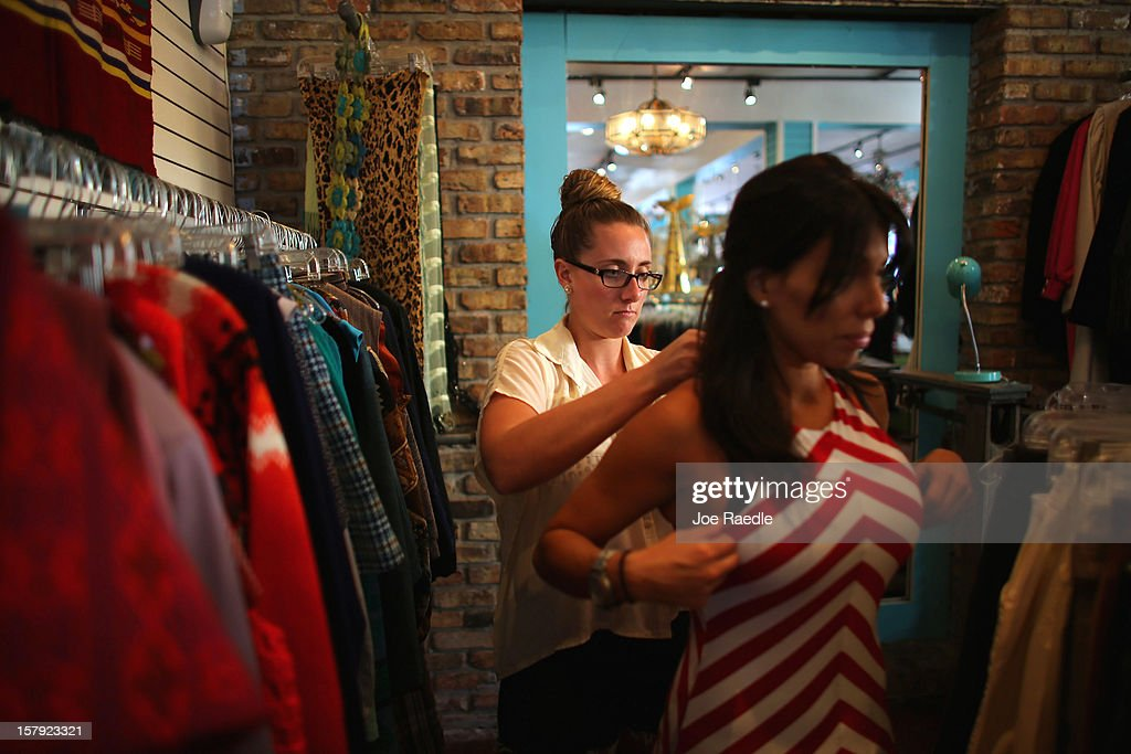 Jacki Stanley (L), who was hired full time by the Sale Rack store three weeks ago, helps Ashley Shapiro as she shops on December 7, 2012 in Miami, Florida. The U.S. Labor Department releases a study showing the economy added 146,000 jobs in November, and the unemployment rate fell to 7.7 percent from 7.9 percent the previous month.