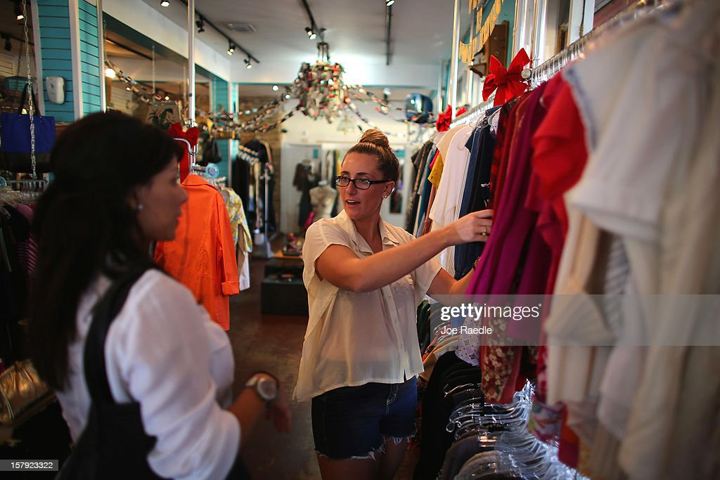 Jacki Stanley (R), who was hired full time by the Sale Rack store three weeks ago, helps Ashley Shapiro as she shops on December 7, 2012 in Miami, Florida. The U.S. Labor Department releases a study showing the economy added 146,000 jobs in November, and the unemployment rate fell to 7.7 percent from 7.9 percent the previous month.