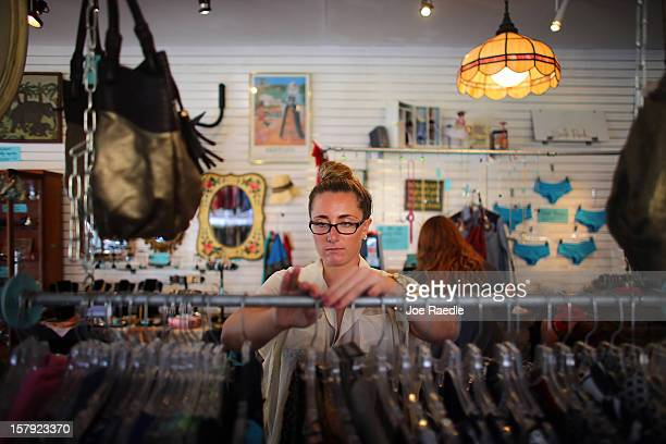 Jacki Stanley who was hired full time by the Sale Rack store three weeks ago organizes the display items on December 7 2012 in Miami Florida The US...