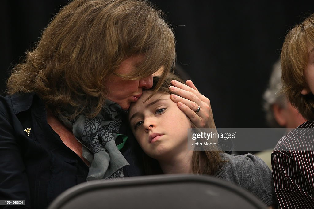 Jackie Barden, whos son Daniel was killed in the Sandy Hook Elementary massacre, kisses her daughter Natalie (10), during a press conference on the one month anniversary of the Newtown elementary school massacre on January 14, 2013 in Newtown, Connecticut. Eleven families of Sandy Hook massacre victims came to the event one month after the shooting to give their support to Sandy Hook Promise, a new non-profit with the goal of preventing such tragedies in the future.