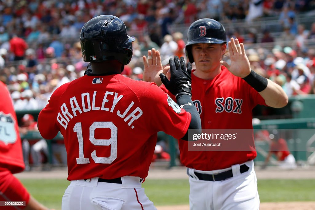 Jackie Bradley Jr. #19 and Brock Holt #12 of the Boston Red Sox celebrate after scoring on a double by Dustin Pedroia #15 against the Washington Nationals in the second inning during a spring training game at JetBlue Park on March 30, 2017 in Fort Myers, Florida. The Red Sox defeated the Nationals 8-1.