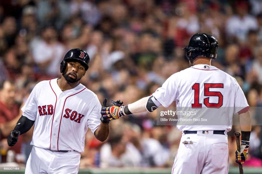 Jackie Bradley Jr. #19 of the Boston Red Sox high fives Dustin Pedroia #15 after scoring during the sixth inning of a game against the Detroit Tigers on June 11, 2017 at Fenway Park in Boston, Massachusetts.