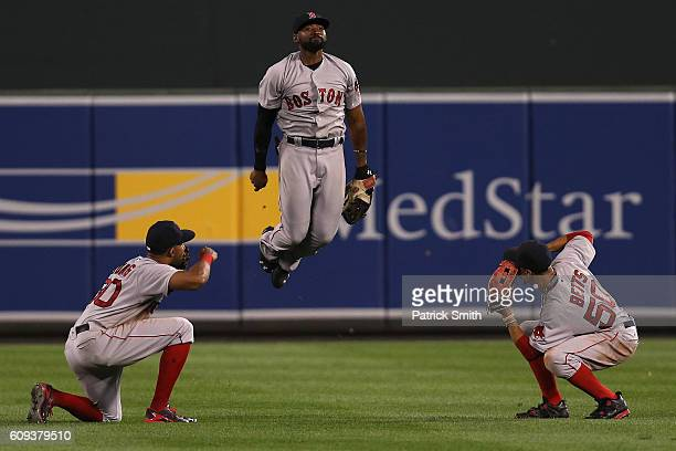 Jackie Bradley Jr #25 Chris Young and Mookie Betts of the Boston Red Sox celebrate after defeating the Baltimore Orioles at Oriole Park at Camden...