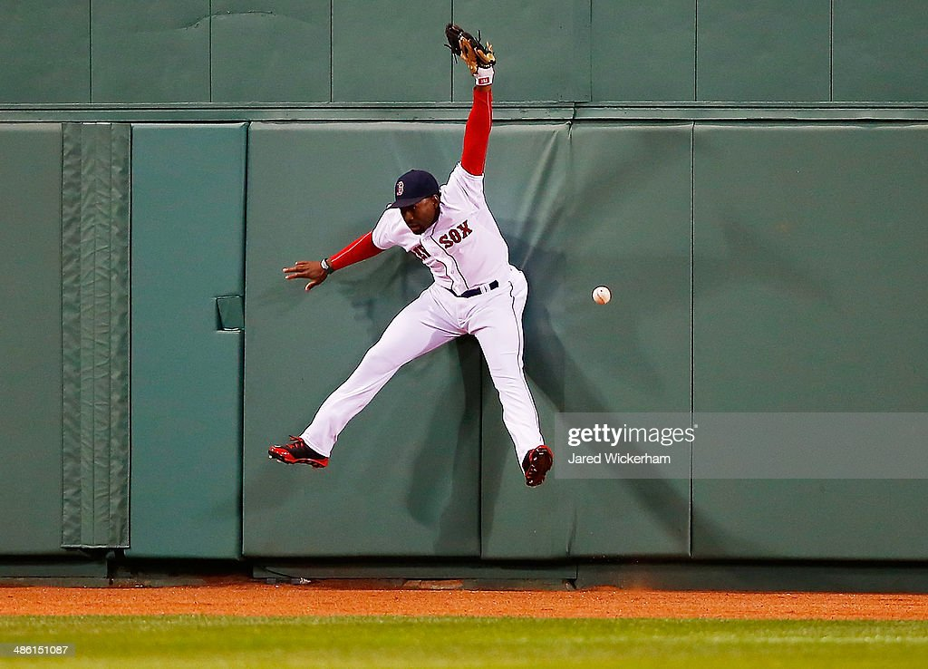 Jackie Bradley, Jr. #25 of the Boston Red Sox jumps up for a fly ball at the center field wall but comes up missing it against the New York Yankees during the game at Fenway Park on April 22, 2014 in Boston, Massachusetts.
