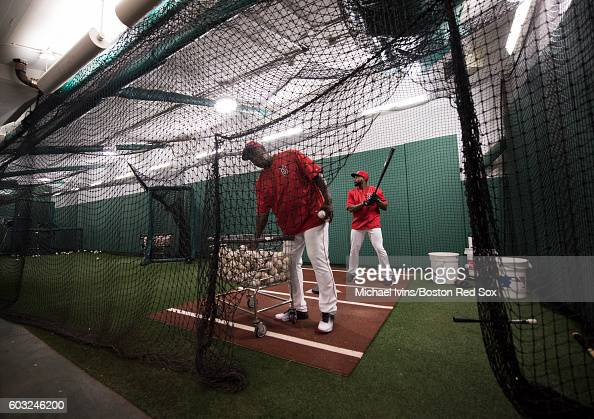 Jackie Bradley Jr #25 of the Boston Red Sox works with hitting coach Chili Davis in the cage before a game against the Baltimore Orioles on September...