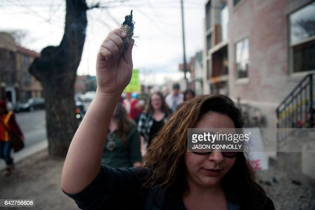 Jackie Carson carries a bundle of burning sage as she marches with demonstrators on February 18 2017 to the First Unitarian Church in Denver Colorado...