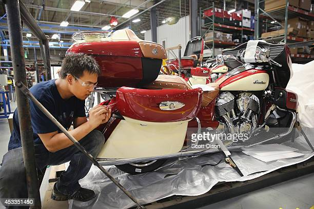 Jackie Donkhong puts finishing touches on an Indian Roadmaster motorcycle at the end of the assembly line at the Polaris Industries factory on August...