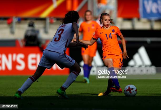 Jackie Groenen of the Netherlands passes under pressure from Sofie Junge Pedersen of Denmark during the Final of the UEFA Women's Euro 2017 between...