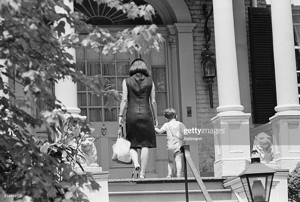 Jackie Kennedy, widow of the late President John F. Kennedy, walks with her son John, Jr. (or 'John-John'), into their Georgetown home.