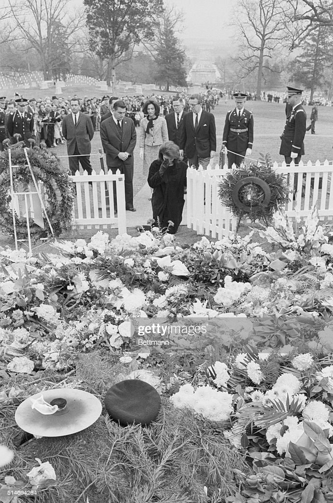 Jackie Kennedy wipes tears away as she kneels at the grave of her late husband, on November 28, 1963. Behind her at the Arlington National Cemetery are Princess Lee Radziwill, her sister; Press Secretary Pierre Salinger, and White House staff John McNally