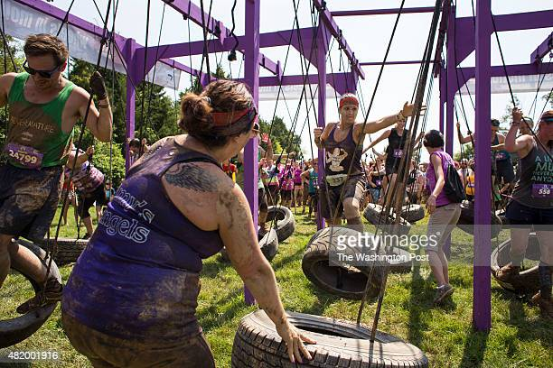 Jackie Lewis of Pottsville Pa assists her teammate Mashawn Leaver of Allentown Pa through a tire swing obstacle during the Mudderalla Mud Run at High...