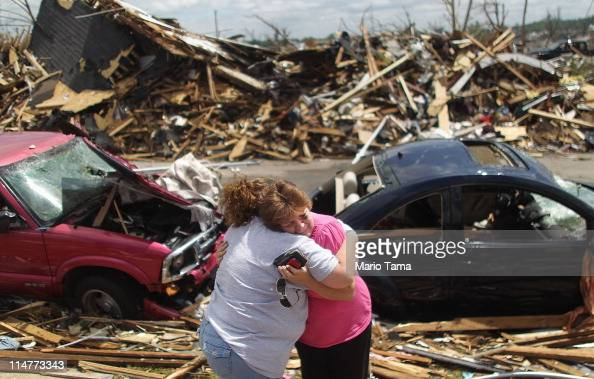 Jackie McGuirk hugs her best friend Dana Roller outside McGuirk's destroyed home after a massive tornado passed through the town killing at least 125...