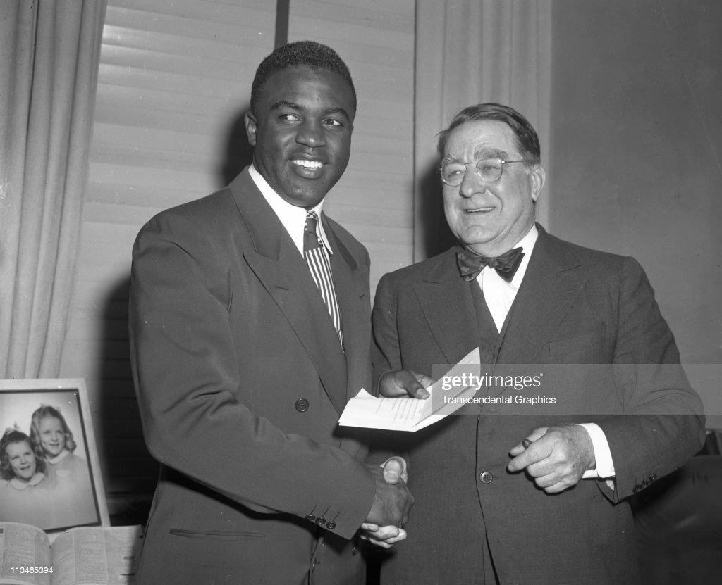 Jackie Robinson and Branch Rickey talk happily after a contract signing meeting in the offices of the Brooklyn Dodgers in Ebbets Field on January 25, 1950 in the Brooklyn borough of New York City.