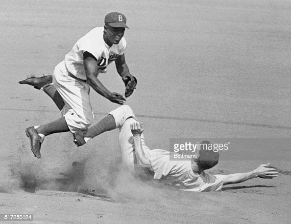 Jackie Robinson leaps into the air in an attempt to make a double play as Hank Sauer slides into second The action took place during the second...